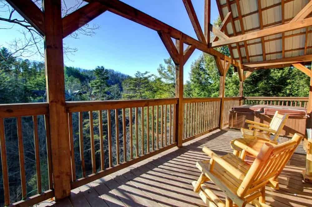 front porch of a cabin on the river in pigeon forge with a hot tub