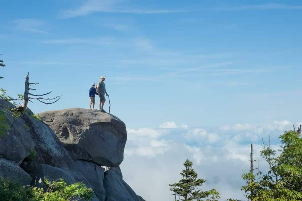 couple exploring Smoky Mountains admiring view from rock overlook