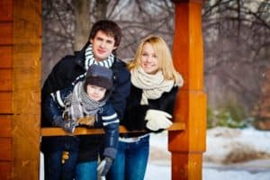 A young family in winter clothing standing on their cabin's porch.