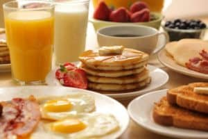A plate of pancakes and other breakfast items.
