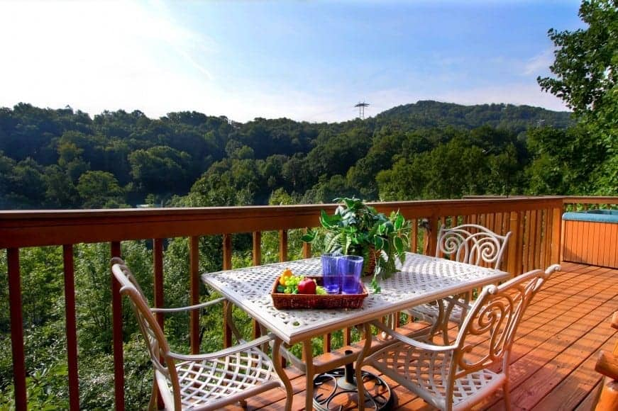 Table and chairs on the deck of a Gatlinburg cabin with mountain views.